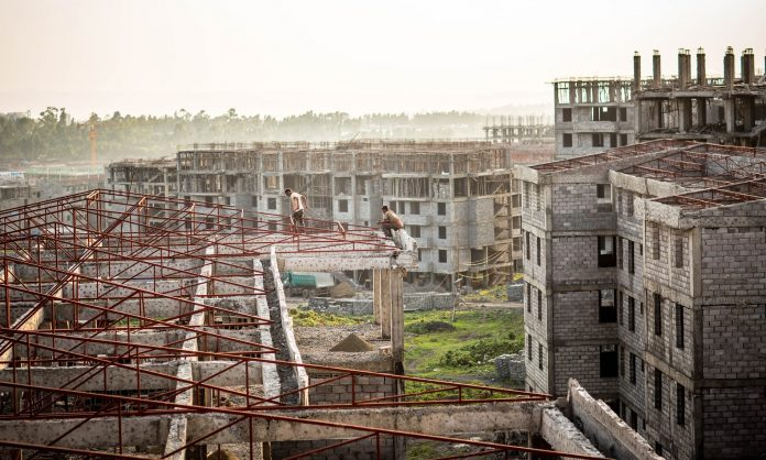 Two construction workers in Koye, the largest condominium site under construction outside Addis Abeba. Photograph: Charlie Rosser